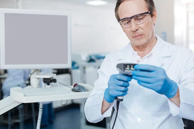 Lo digo en serio. persona del sexo masculino pensativo con gafas protectoras y presionando los labios mientras realiza análisis de sangre