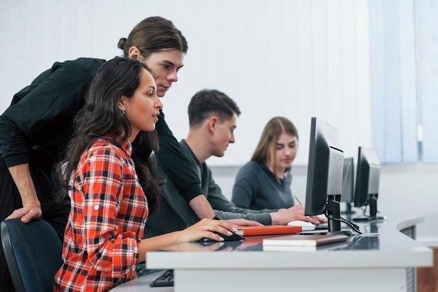 Lo estoy haciendo bien. grupo de jóvenes en ropa casual que trabajan en la oficina moderna
