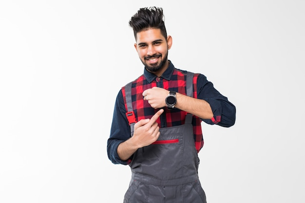 Lo hacemos a tiempo. joven confidente manitas con barba en general azul y camiseta roja de pie y mostrando la hora en su reloj de pulsera aislado en el espacio en blanco
