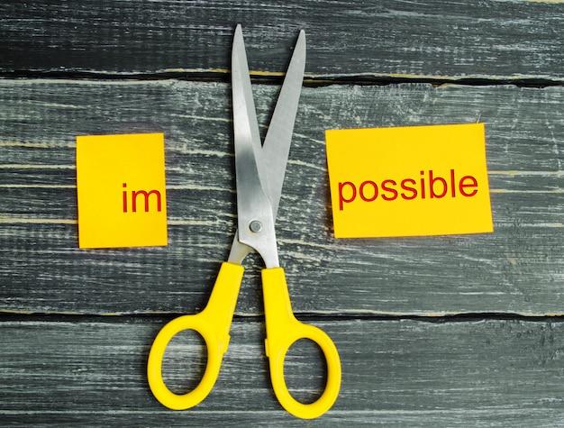 Lo imposible es el concepto posible. tarjeta con el texto imposible, tijeras cortan una palabra a ellos.