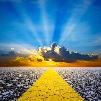 A lo largo de la carretera con el cielo del atardecer y el fondo de rayos de sol