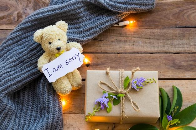 Lo siento escritura de tarjeta de mensaje con caja de regalo, luz, oso de peluche y bufanda de lana de tejer en madera