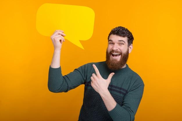 ¿lo ves? un hombre sonriente señala el discurso de burbuja que está sosteniendo.