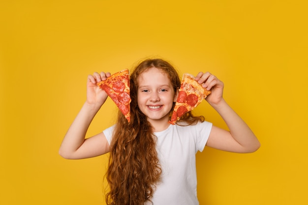 La loca chica rizada sostiene dos rebanadas de pizza cerca de sus ojos y saca la lengua.