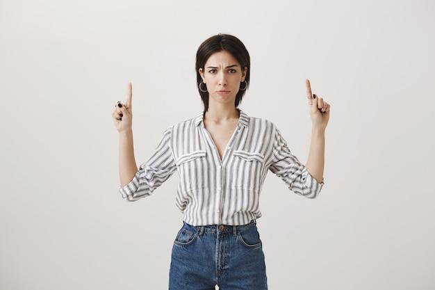 Loca mujer decepcionada apuntando con el dedo hacia arriba, diciendo malas noticias