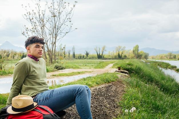 Localización masculina joven hermosa del viajero en el banco del río