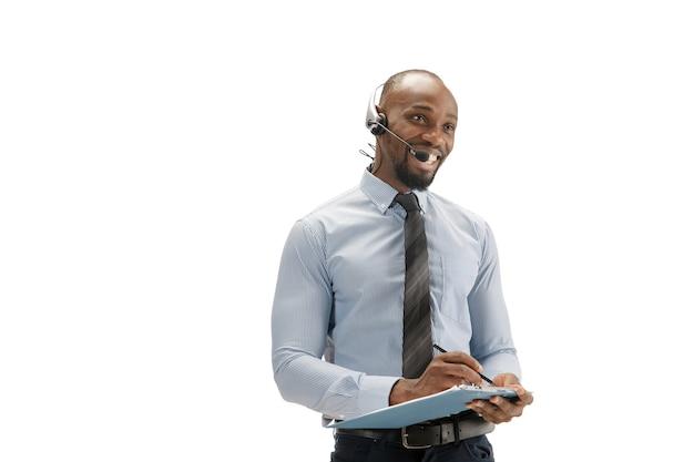 Locamente molesto, estresado. consultor de centro de llamadas afroamericano joven con auriculares en estudio blanco.