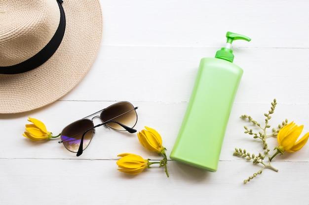 Loción corporal y gafas de sol en el cuadro blanco