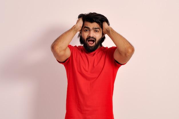 Loco gritando hombre desgarrando su cabello gritando con la boca abierta tomados de la mano en la cabeza