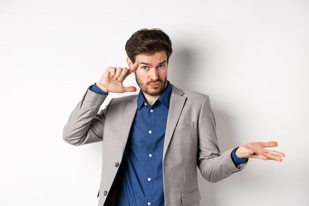 Estas loco. hombre joven en traje señalando con el dedo a la cabeza para regañar error extraño o estúpido, encogiéndose de hombros confundido, de pie sobre fondo blanco.
