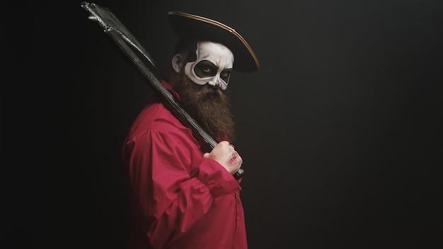 Loco con maquillaje disfrazado de pirata con hacha para fiesta de halloween.