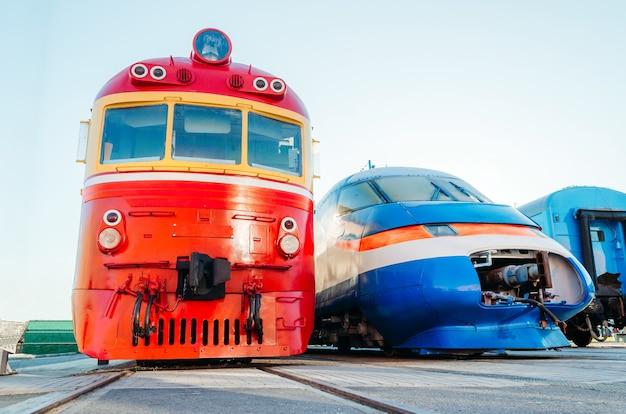 Locomotoras de trenes antiguos y modernos de perfil se muestran en una fila
