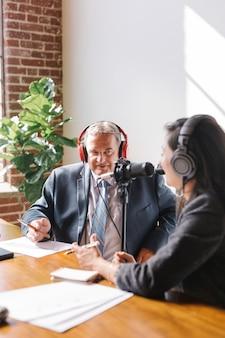 Locutor femenino entrevistando a su invitado en un estudio.