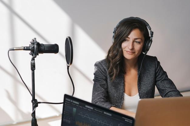 Locutor de radio femenino transmitiendo en vivo en un estudio.