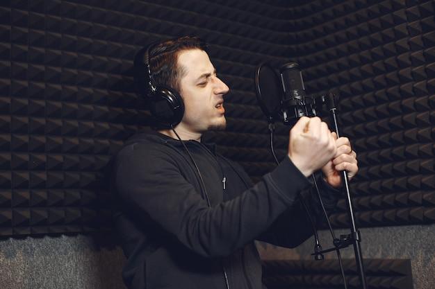Locutor de radio gesticulando mientras graba un podcast en un estudio de radio.