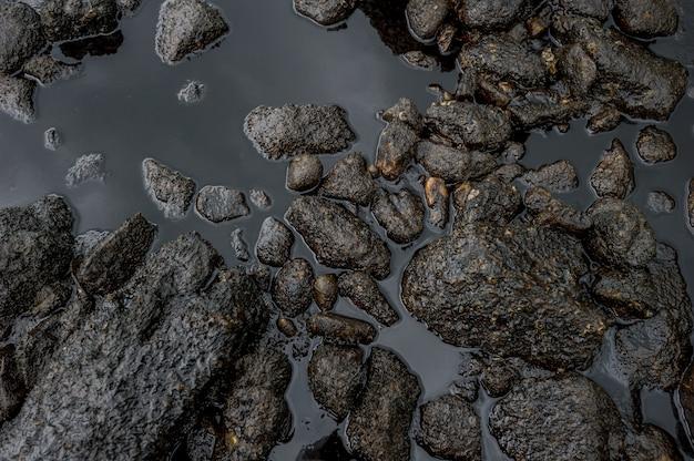Lodos de petróleo que contaminan el mar durante el desastre del derrame de petróleo en la isla de samet, rayong, tailandia.