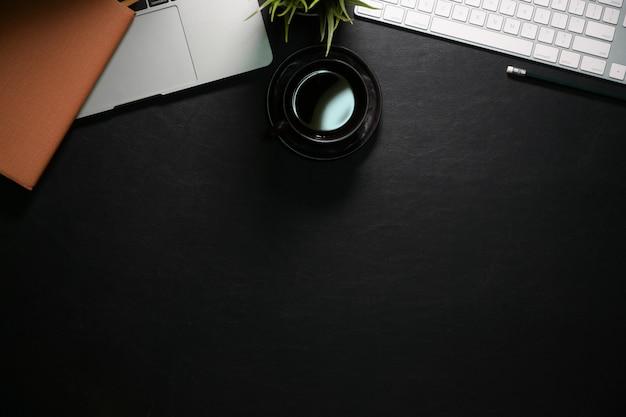 Loft espacio de trabajo de cuero oscuro con taza de café negro