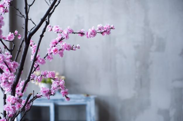 Loft interior con muro de hormigón y árbol de sakura rosa