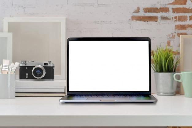 Loft mesa de escritorio de oficina de madera con laptop, póster, cámara vintage y suministros.