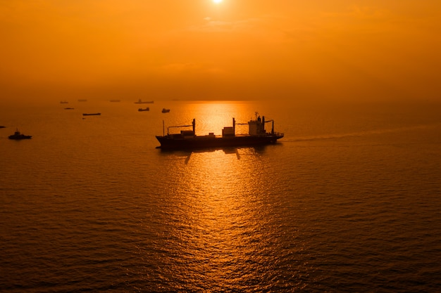 Logística de silueta enviando carga mar abierto y sobre el fondo del atardecer