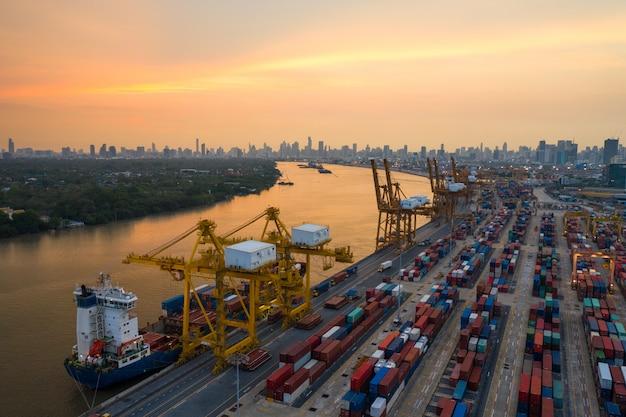 Logística y transporte de buque de carga de contenedores y avión de carga con puente grúa en funcionamiento en el astillero al amanecer, exportación logística de importación y fondo de la industria del transporte