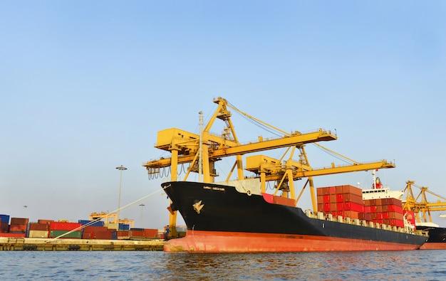 Logística y transporte del buque de carga de contenedores con puente grúa en funcionamiento en el astillero en la noche