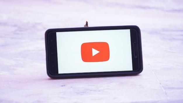 Logotipo de la pantalla de presentación de youtube en móvil y móvil en mano