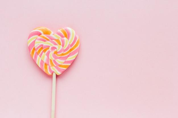Lollipop en forma de corazón rayado grande y confeti de confitería sobre un fondo rosa espacio de copia