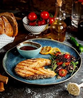 Loncha de pescado frito con hierbas y verduras y salsa