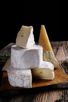 Loncha de queso de cabra camembert y queso brie en la mesa de madera oscura