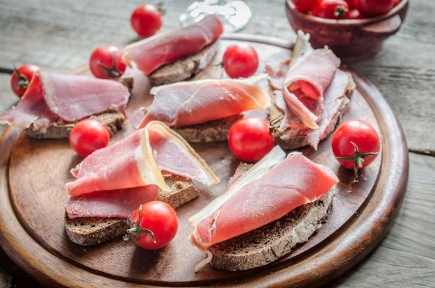 Lonchas de jamón italiano sobre la plancha de madera