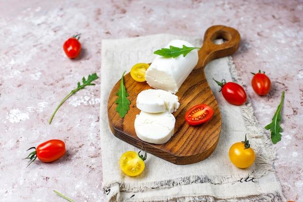 Lonchas de queso de cabra sobre tabla de madera con ruccola, tomates cherry. listo para comer.