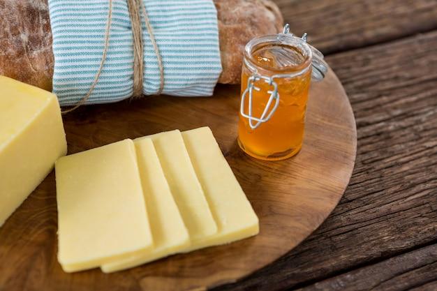Lonchas de queso, pan y mermelada de frutas sobre tabla de madera