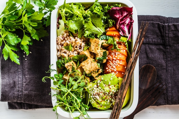Lonchera con comida vegana saludable. bento box con arroz, camote, tofu y verduras.