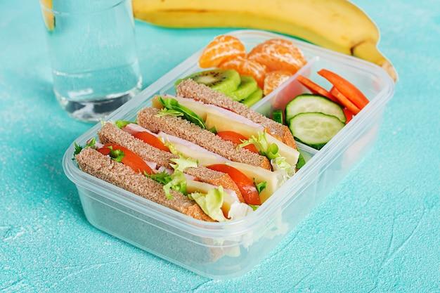 Lonchera escolar con sandwich, verduras, agua y frutas en la mesa.