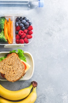 Lonchera escolar con sándwich de verduras bayas de plátano en la mesa gris saludable