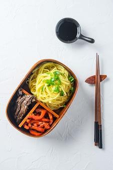 Lonchera de fideos de carne bento en mesa blanca.