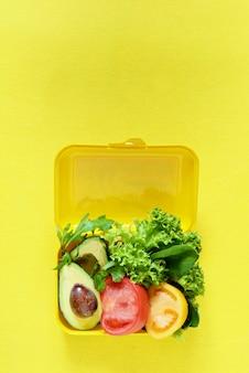 Lonchera con una merienda de lechuga, tomate, aguacate en una pared amarilla. concepto de alimentación saludable vamos vegano. sabrosa comida vegetariana en caja de plástico.