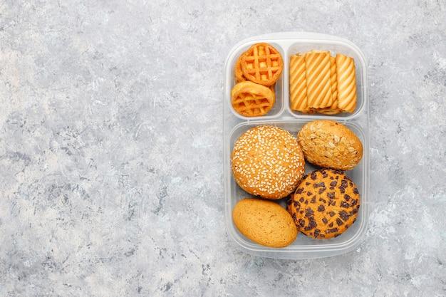 Lonchera poco saludable con galletas, waffles, muffins en superficie de concreto