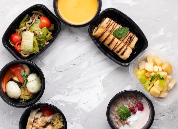 Lonchera saludable en cajas de plástico, sopa de crema de calabaza, huevos de codorniz y ensalada de verduras, postre en contenedores de comida. concepto de dieta, nutrición