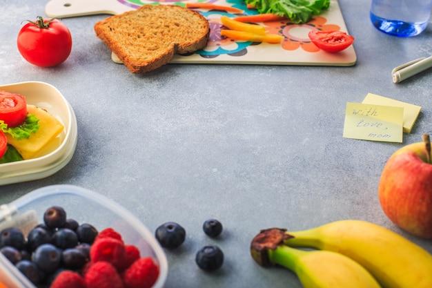 Lonchera con sándwich, bayas de plátano y zanahorias cortadas en espacio gris para texto