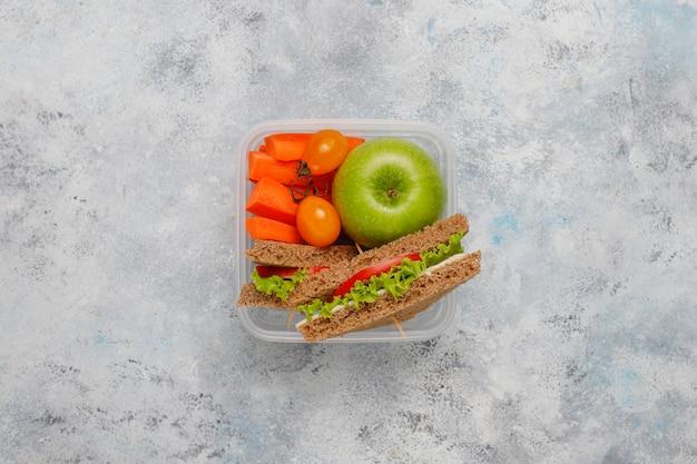 Lonchera con sandwich, verduras, frutas en blanco.