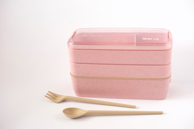 Lonchera vacía rosa sobre un fondo blanco con cuchara y tenedor