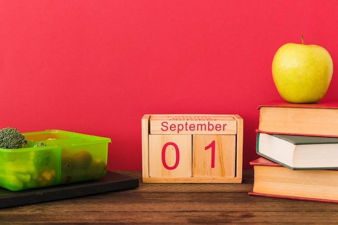 Lonchera y calendario cerca de frutas y libros