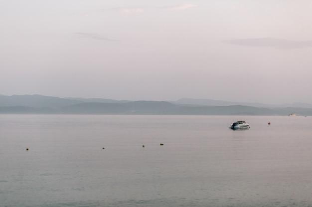 Lonely barco flota en el mar bajo el cielo gris