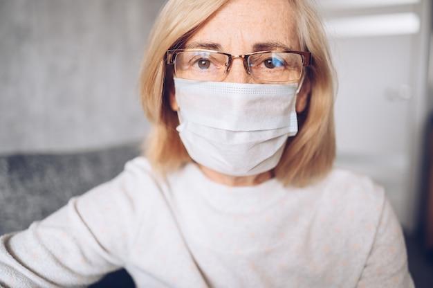 Lonely deprimido, triste, anciana, anciana, anciana con máscara de protección facial, anteojos y guantes médicos, sentada en su casa en cuarentena de auto aislamiento durante la pandemia de coronavirus covid19. concepto de quedarse en casa
