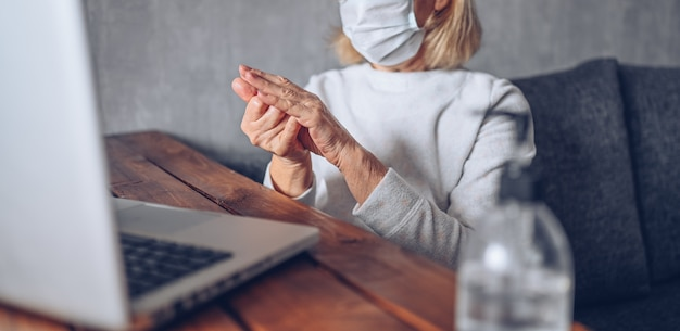 Lonely triste anciana senior en máscara médica facial utilizando desinfectante líquido antibacteriano de mano con computadora portátil en casa cuarentena de auto aislamiento durante la pandemia de coronavirus covid19. quedarse en casa