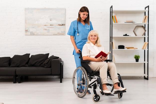 Long shot enfermera cuidando a mujer en silla de ruedas