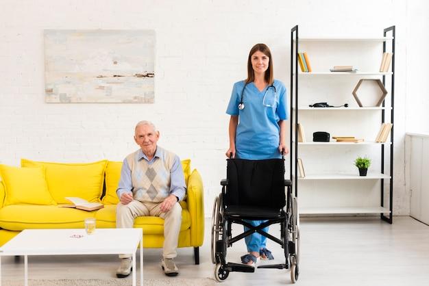 Long shot enfermera sosteniendo una silla de ruedas para anciano