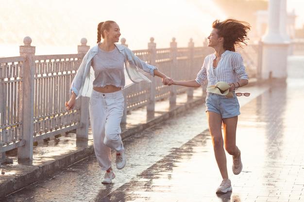 Long shot mujeres jóvenes corriendo y tomados de la mano.